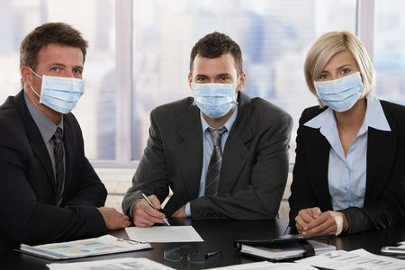 fearing: Business people fearing h1n1 swine flu virus wearing protective face mask during meeting at office.