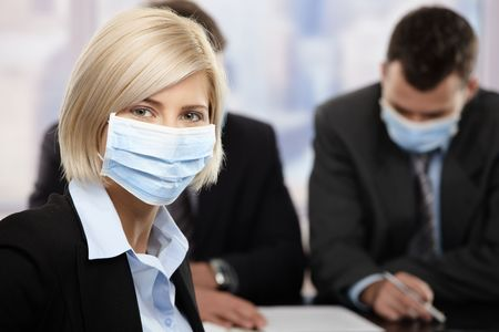Businesswoman fearing h1n1 swine flu virus wearing protective face mask during meeting at office. photo
