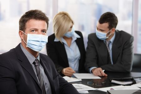 fearing: Businessman fearing h1n1 swine flu virus wearing protective face mask during meeting at office.