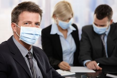 epidemic: Businessman fearing h1n1 swine flu virus wearing protective face mask during meeting at office.