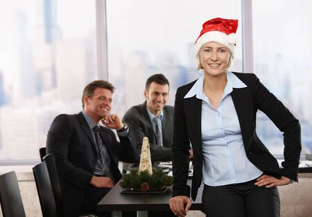 Happy young businesswoman wearing Santa Claus hat at office, looking at camera, smiling. Businessmen in background. Stock Photo - 5899174