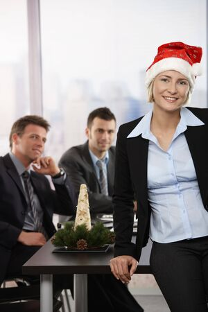 Happy young businesswoman wearing Santa Claus hat at office, looking at camera, smiling. Businessmen in background. photo