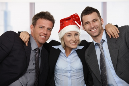Happy young businesswoman wearing Santa Claus hat at office hugging friends, looking at camera, smiling.  photo