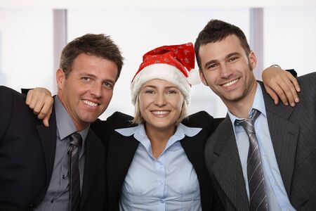 office wear: Happy young businesswoman wearing Santa Claus hat at office hugging friends, looking at camera, smiling.  Stock Photo