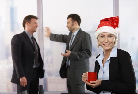 Happy young businesswoman sitting on desk at office wearing Santa Claus hat, looking at camera, smiling. Businessmen in background. photo