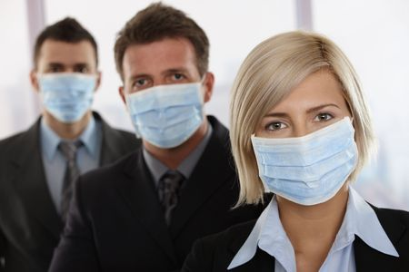 protective wear: Business people fearing h1n1 swine flu virus wearing protective face mask and standing in a row. Stock Photo