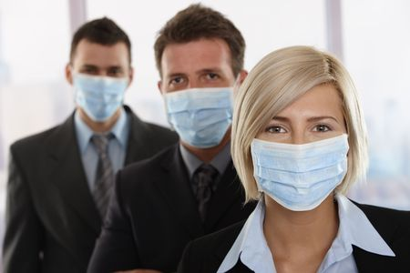 fearing: Business people fearing h1n1 swine flu virus wearing protective face mask and standing in a row. Stock Photo
