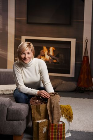 Happy young woman siiting on sofa at home taking out clothes of shopping bags. smiling. Stock Photo - 5899182
