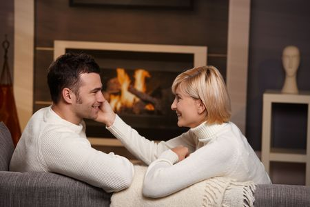 Young romantic couple sitting on sofa in front of fireplace at home, looking at each other, smiling. photo