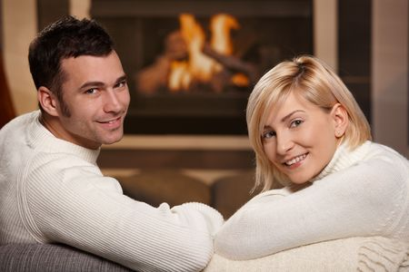 cosy: Young romantic couple sitting on sofa in front of fireplace at home, looking back, smiling. Stock Photo