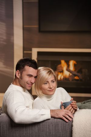 tea cosy: Young love couple hugging on sofa in front of fireplace at home, looking away, smiling. Stock Photo