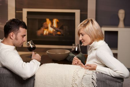 warm cloth: Young romantic couple sitting on sofa in front of fireplace at home, drinking red wine. Stock Photo