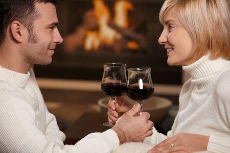 Joven pareja romántica, sentado en el sofá en frente de la chimenea en casa, beber vino tinto.