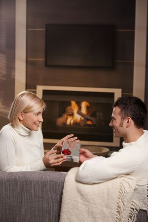 Young romantic couple sitting on couch in front of fireplace at home, man giving gift, side view. photo