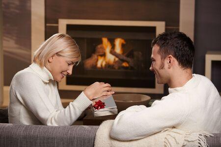 Young romantische Pärchen auf der Couch vor dem Kamin zu Hause, Mann geben Geschenk, Seitenansicht. Standard-Bild - 5899221
