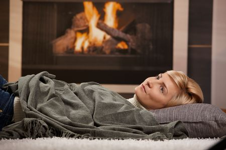 winter break: Woman resting at home lying on floor in front of a fire place, Stock Photo