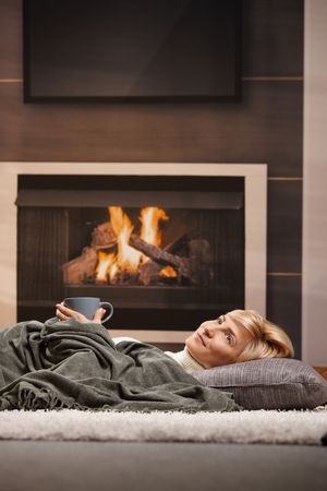 warm drink: Woman resting at home lying on floor in front of a fire place, Stock Photo