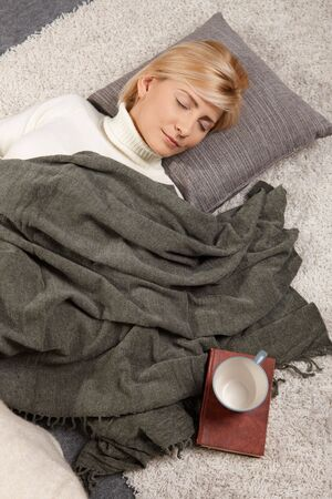 white blanket: Woman sleeping on floor at home
