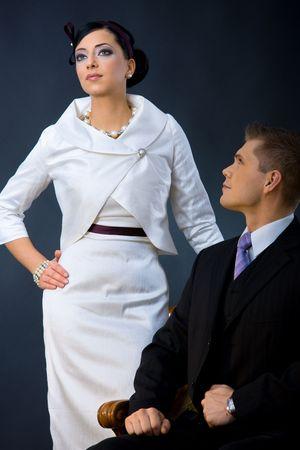 traje de gala: Retrato de la joven pareja vestidos con ropa elegante. Mujer vistiendo la camiseta blanca de c�ctel con chaqueta, hombre vistiendo traje oscuro de tres piezas.