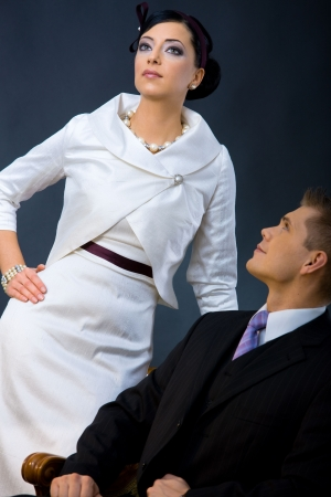 formal attire: Portrait of young couple dressed in elegant clothes. Woman wearing white cocktail shirt with jacket, man wearing three-pieces dark suit, looking up.