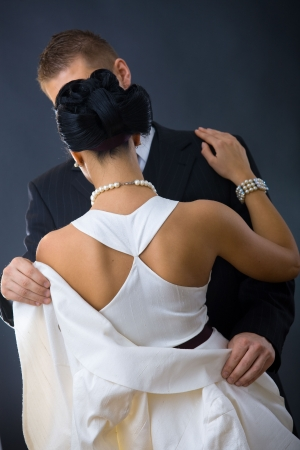 evening gown: Back of woman wearing white evening dress. Her boyfriend holding his jacket. Stock Photo