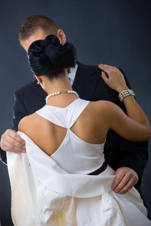 buonanotte: Retro della donna che indossa abito da sera bianco. Suo fidanzato detiene la sua giacca.