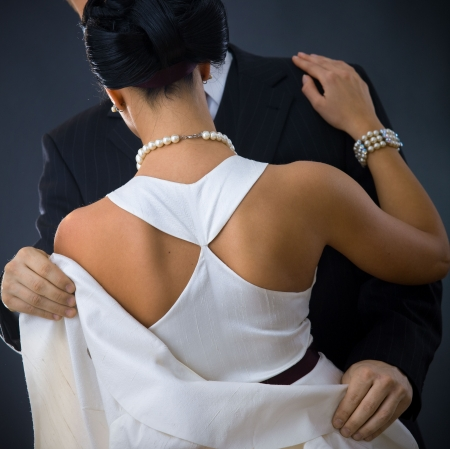 formal attire: Back of woman wearing white evening dress. Her boyfriend holding his jacket. Stock Photo