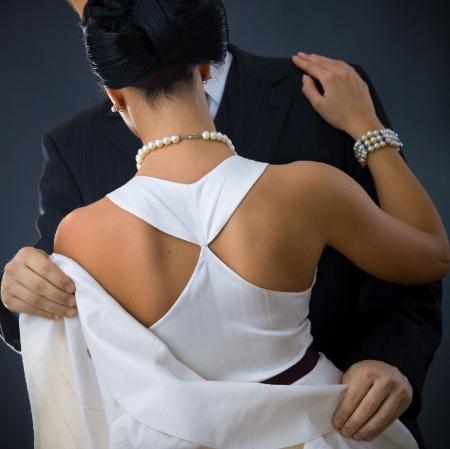 EVENING DRESS: Reverso de la mujer con vestido de noche blanco. Su novio sosteniendo su chaqueta.