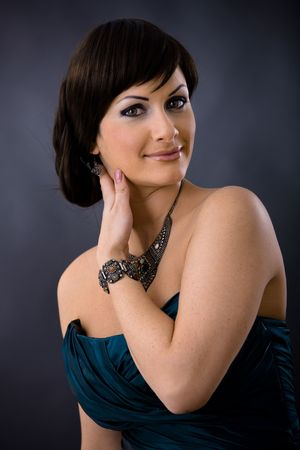 Closeup portrait of beautiful young woman wearing dark blue evening dress with necklace and bracelete, smiling and looking at camera. photo