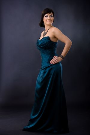 Studio portrait of beautiful young woman wearing dark blue evening dress, posing with hands on hip, smiling. photo