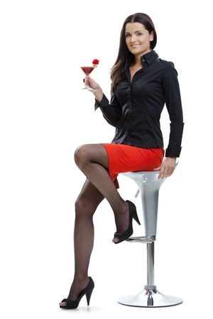 Sexy young woman sitting on bar chair, holding glass of cocktail in hand. photo