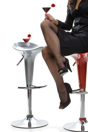 Woman wearing black skirt and stockings holding glass of cocktail on her knee. photo
