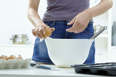 Female hands breaking eggs into a bowl. photo