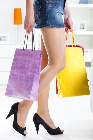 pies sexis: Piernas largas femeninas en medias. Manos sosteniendo coloridos bolsas de la compra.