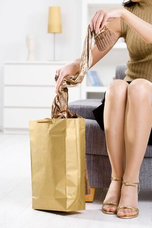 long feet: Closeup photo of female hands packing out of shopping bag, legs in stockings and shoes.