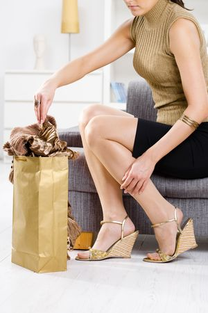 Elegant young woman sitting on couch, packing out from shopping bag. photo