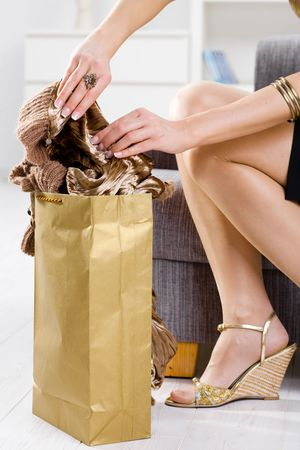 Closeup photo of female hands packing out of shopping bag, legs in stockings and shoes. photo