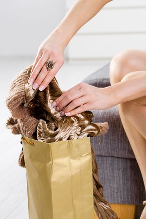 Closeup photo of female hands packing out from shopping bag. Legs in stockings and gold color shoes. Stock Photo - 5932541