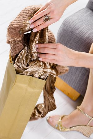 Closeup photo of female hands packing out from shopping bag. Legs in stockings and gold color shoes. photo