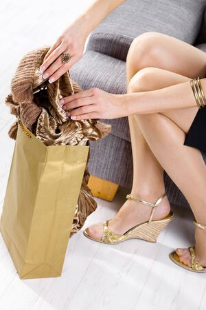 Closeup of female hands packing to shopping bag and legs in stockings and shoes. photo