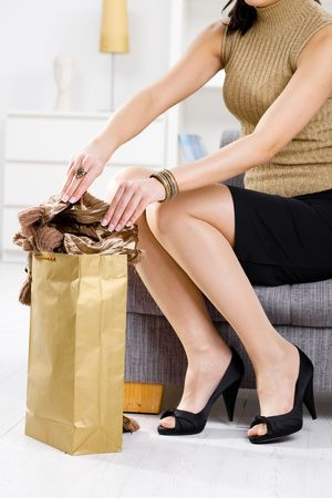 Elegant young woman sitting on couch, packing out from shopping bag. Stock Photo - 5932542