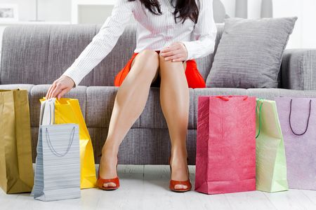 medias mujer: Joven sentado en el sof� despu�s de d�a de compras, embalaje coloridos bolsas de la compra.