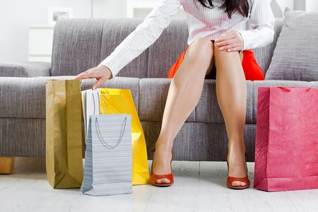 Young woman sitting on couch after day of shopping, packing colorful shopping bags. Stock Photo - 5932552