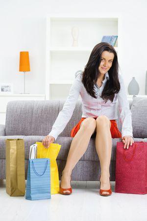 mujeres sentadas: Joven sentado en el sof� despu�s de d�a de compras, embalaje coloridos bolsas de la compra.