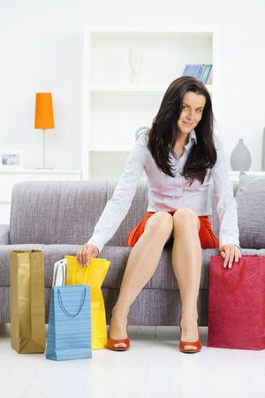 Young woman sitting on couch after day of shopping, packing colorful shopping bags.  photo