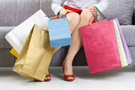 Young woman sitting on couch after day of shopping, packing colorful shopping bags. Stock Photo - 5932545