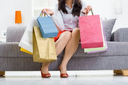 Young woman sitting on couch after day of shopping, holding colorful shopping bags.  photo