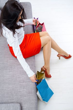 Young woman sitting on couch after day of shopping, packing colorful shopping bags. Overhead shot. Stock Photo - 5931771