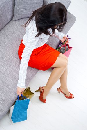 Young woman sitting on couch after day of shopping, packing colorful shopping bags. Overhead shot. Stock Photo - 5931773