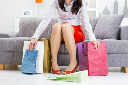 Young woman sitting on couch after day of shopping, surrounded with colorful shopping bags.  photo